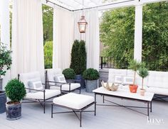 The terrace acts as an outdoor oasis in the busy city. A pendant from Bevolo Gas and Electric Lights hovers above Restoration Hardware furniture, and Perennials white drapery fabric from David Sutherland hangs against a custom pergola designed by Labrum. The planters are from Jayson Home.