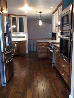 Custom kitchen with Lennon granite countertops, subway tile and glass mosaic back splash, corner glass cabinet and wood floors, Caldera Design LL