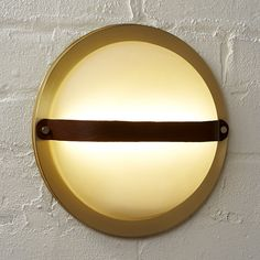 Shop hemisphere wall sconce.   Classic ship portholes shine anew in this modern maritime design by Mermelada Estudio.  Inspired by iconic ship windows, ours is made modern in brushed brass with a sophisticated leather strap.