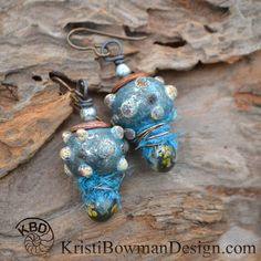 Amazing Bumpy Lampwork Beads by HavanaBeads with wonderful Lampwork Headpins by Numinosity with some beautiful coodinating Sari Silk in between. Copper Sea Urchin bead caps topped with a pretty blue Czech Glass Beads. Hypoallergenic Niobium Earwires top it all off.
