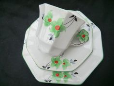 A rare floral handled Art Deco tea trio Made by Melba china Entirely hand painted in stylised green flowers with bright orange centres and black