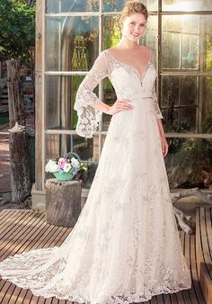 While you may not want rain on your wedding day, our Rayne gown is a different story. Boho brides will swoon at the three-quarter bell sleeves and exquisite foliage patterned embroidered lace of this bohemian beauty. A modern touch is provided by the low plunging illusion V-neckline, all tied together with a ribbon sash at the natural waist.