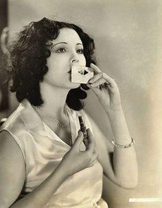 1920s silent film actress Raquel Torres using a lip stencil