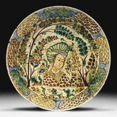 A KUBACHI POLYCHROME POTTERY DISH NORTH IRAN, EARLY 17TH CENTURY With sloping rim and short foot, the white ground painted in blue, green, red, brown and ochre with a central bust portrait of an elegant youth wearing a large turban and holding in his left hand a floral spray, the youth flanked with further floral sprays and waving trees, the rim with cartouches of colourful fish-scale motif on blue ground, hair cracks