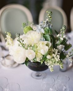 Tiny glass vessels helped arrangements of astrantia, white scilla, delphinium, parrot tulips, peonies, stock, rose, viburnum, thlaspi, and larkspur look lush and dramatic at Leoma and Gary's England affair.