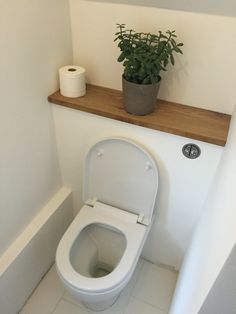 Downstairs WC cloakroom with concealed cistern and oak shelf under stairs