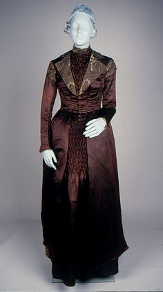 Dress Accession Number: 1996.24.123-A-B Date Made: c.1880-1881 Description: Dress; maroon and brown figured silk bodice (A) and skirt (B) with smocked panels. The bodice has a high neckline with short standing collar edged with white silk and metal braid. The bodice opens down the center front and fastens with 15 decorative, fabric covered buttons.