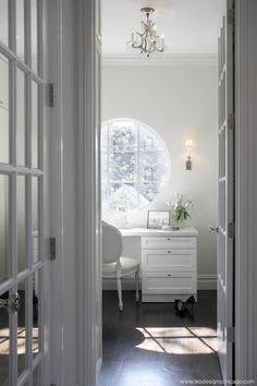 A long home office features a light gray built in desk adorned with brushed brass pulls topped with charcoal gray quartz and lined with a white woven chair placed atop a white and gray cement tile floor. White Interior, Decor, Home, White Cottage, White Rooms, Beautiful Homes, House Interior, White Interior Design, White Elegance