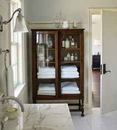 Using Vintage Furniture in your Bathrooms. It is a great option for all the Bathroom Storage Needs we have. Love the Contrast between this White Bathroom and then the Deep Wood Vintage Storage Furniture Piece. - Home Design Bad Inspiration, Bathroom Inspiration, Bathroom Ideas, Furniture In Bathroom, Bathroom Cabinets, Glass Bathroom Cabinet, Bathroom Trends, Bathroom Vanities, Bathroom Fixtures