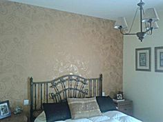 Papel en pared principal del dormitorio, armonizando con el tono del resto de las paredes, aportando un toque de elegancia el dorado del dibujo que refleja la luz de la ventana