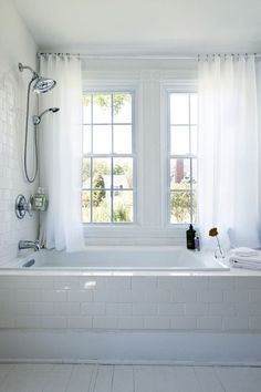 White, breezy curtains surround the guest bathtub with generous views of the lush property.