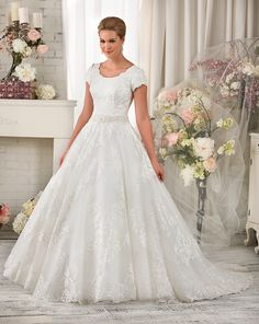 A fairytale ball gown fit for a princess. Ornate lace covers the bodice and falls into a lattice pattern over the full skirt and train. The slightly dropped waist is embellished with dazzling stones and beads. | Bonny Bliss Bridal Style: 2412 | Modest Wedding Dress