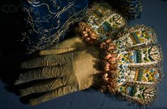 A pair of gauntlet gloves that once belonged to Elizabeth I are decorated with embroidered flowers on the cuff.