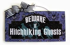 Haunted Mansion sign. Beware of Hitchhiking Ghosts.