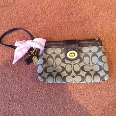 Coach Wristlet with pink bow, 2 big pockets Great brown leather Wristlet with classic Coach print! Metal clasp. Fun pink bow & brown + gold Coach key chains. 2 pockets - one in the front & main pocket. Can hold a lot! Coach Bags Clutches & Wristlets