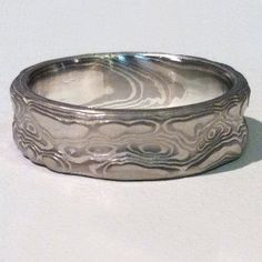 """This Mokume Gane ring is patterned in the """"Guri Bori"""" style which leaves the carved surface as relief showing the layers like topographic lines which match the contours of the carving.  Reminiscent of swirling water, clouds, wind blown snow or canyons this ring has a unique tactile beauty.  Shown here in a 6mm wide band with the palladium and silver metal combination and an etched finish."""