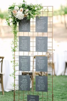 Gold grid escort card stand with greenery and flowers on the side and dark drey paper with table names and numbers in white calligraphy, film by Cavin Elizabeth Photography for a Gainey Vineyards Wedding Seating Plan Wedding, Wedding Signage, Rustic Wedding, Wedding Table Names, Seating Plans, Tuscan Wedding, Wedding Seating Charts, Wedding Table Assignments, Wedding Name