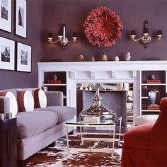 (bhg.com) Touch of Glamour - Purple adds a glamorous touch to any room. Here, a rich shade of gooseberry coats the living room walls. Large amounts of white on the moldings and artwork break up the color, while the red accents bring out the hue's red undertones. Dark colors work well in rooms flooded with natural light throughout the day.