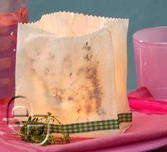 Thymian-Licht  Duftlicht einfach hergestellt: Zwei Butterbrottüten ineinander stecken und mit der Zackenschere kürzen. In den Zwischenraum der Tüten frische Kräuterzweige stecken. Mit Karoband umkleben und Glas mit Teelich hineinstellen.