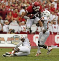 OU's Trey Millard (33) leaps over UT's Mykkele Thompson (2) and pushes away Adrian Phillips (17) in the second quarter during the Red River Rivalry college football game between the University of Oklahoma (OU) and the University of Texas (UT) at the Cotton Bowl in Dallas, Saturday, Oct. 13, 2012. OU won, 63-21. Photo by Nate Billings, The Oklahoman