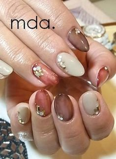 Nail art neutral browns and pink peach nude gel nail colors. Glitter and jewel accent nail decals. Everyday nails
