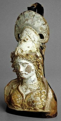 """ca. 475-350 BCE. Bust of Athena, wearing her large helmet tilted back over curly locks; beaded necklace. Painted and gilt terracotta Lekythos 8."""" The British Museum"""