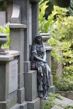 #Kiel In fließende, lange Gewänder gekleidet,sitzt die junge Frau auf einem Sockel der Grabstelle. Trauernde junge Frau (Bronze). Südfriedhof, Saarbrückenstraße, 24114 Kiel.