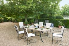 "Fantastical Enclaves ""My inspiration for the garden was medieval, to go with the house, but it's not a faithful copy,"" Lévy-Alban explains. ""Gardens should be fantasy.""    Table and chairs, Heveningham Collection. Baccarat stemware."