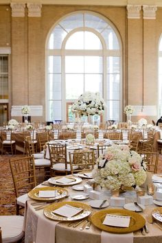 Spectacular wedding reception at Union Station Dallas. Floral arrangements of hydrangea, roses and gardenias. Photography by Thisbe Grace. China, crystal, silver and chairs from POSH Couture Rentals Dallas.