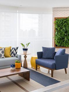 Decoração de apartamento aconchegante e atemporal. Na sala sofá azul, poltrona azul, mesa de centro de madeira e adornos.