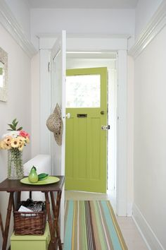Prefect! A bamboo table and basket keep this front hall stylish and organized.    The lime-green door and striped mat in this entryway add modern punch to country charm. Accessories pick up the same hue.    Photographer: Angus Fergusson