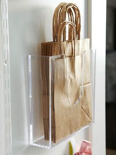 Office supply stores are a treasure trove of mostly inexpensive storage items that help to keep things vertical, horizontal, or divided. These clear plastic display caddies hold paper bags; attach the caddy to the back of the door with a very slim screw or adhesive tacks. good idea for GIFT BAGS too