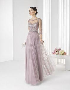 Необычное вечернее платье прямого силуэта выполнено в легком лавандовом оттенке, полном романтичного настроения. Сделать образ максимально элегантным помогает комбинация прозрачной ткани, скрывающей декольте и создающей облегающие рукава, и вышивки в тон ткани, располагающейся по всему верху платья. Лаконичную юбку из нескольких слоев шифона украшают вертикальные складки, спускающиеся от линии талии вниз.