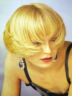 Blonde hair was cut into a short bob and blow-dried smooth and brushed onto the face