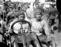 J. F. Gelnaw, auto driver, at the Elgin National Road Races sitting next to his mechanic, circa 1910. Gelnaw and his mechanic were most likely driving a Fal-Car, according to their sweaters. Fal-Car's were manufactured between 1909 and 1914 and were known as
