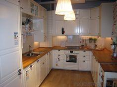 Ładna jasna kuchnia ze stylowymi szafkami i dodatkami. Są to meble kuchenne BODBYN ...