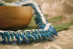 The Haiku orchid lei is a combination of milky white petals woven with tinted blue orchids and hints of purple. Featuring fluttering edges for a comfortable