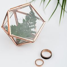 This modern mini glass geo ring box is a trendy addition to your wedding that will showcase the rings in a unique way. Use an imaginative filler such as mini pebbles, flower petals, moss or even a succulent plant to nestle the wedding rings while inside. Featuring a hinged lid, each hand soldered geometric shape is made from copper coloured metal with a charming patina and clear glass. The result is a chic keepsake box that can be used as a wedding ring box, jewellery box or a mini glass…