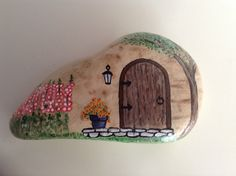 Rock painted cottage with hollyhock flowers by H. Reardon