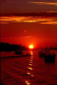 A stunning orange sunset over a Maine harbor.