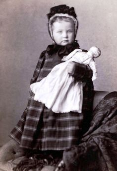 Vintage photo of a little girl and her doll circa 1910.