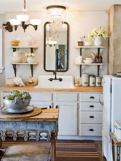 Not Your Average Kitchen  Lux accents add personality to this kitchen. Two chandeliers hang in this kitchen, one fashioned from crystals and another painted to match the iron brackets, cabinet hardware, and faucet.The island is a pine table that edged with tin Victorian flashing.