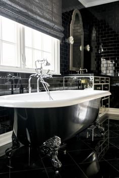 Take a Look at Kylie Jenner's Stunning Calabasas Home  - HouseBeautiful.com The bathroom is over-the-top chic with black subway tiles and a clawfoot bathtub in black and white. #celebritybathrooms #kyliejenner