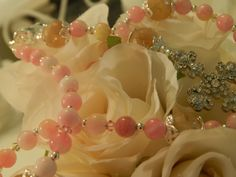 Watercolor Rosary Pink and Yellow •	Decade beads warm Semi-Precious Watercolor Pink and Yellow Jade Gemstones (8mm) •	Our Father beads gorgeous (12mm) Semi-Precious Citrine Gemstones accented capped with silver petal caps •	Sterling Silver round spacer beads throughout compliment the beauty of this piece •	This Piece is shown with Crystal Encrusted Cross and Swarovski Clear Crystal Center Flower