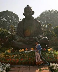 SERENITY:  A worker waters plants around a statue of Mahatma Gandhi inside the premises of Parliament. (Saurabh Das, AP)