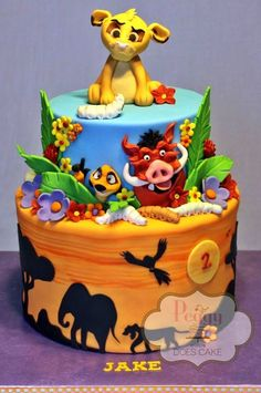 This Fabulous Lion King 2nd Birthday Cake was made by Peggy Does Cake. The bottom layer of this Disney cake is painted orange to represent an African sunset. Silhouettes of trees, elephants, lions, and birds are on the side of this cake layer. A yellow moon has a red number...