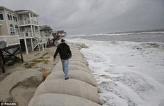 Documenting a disaster: Cage Deal, a senior at Whiteville High School, walks to get a better vantage point as he gets video footage of the waves of Hurricane Sandy in Ocean Isle Beach, North Carolina