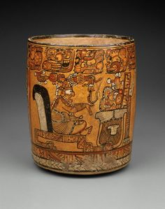 Large vase painted with a scene depicting the Hero Twins Hun Ajaw and Yax Balam conversing with the deity Its'amnaj, all of whom are seated inside a building. Its'amnaj gestures towards a large basket on top of which sits a skeletal head, jewelry and clothing that likely are those of the Hero Twins' father the Maize god (Hun Hun Ajaw).