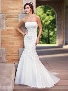 Strapless tulle trumpet gown features a dropped waist bodice adorned with directionally draped ribbon work and hand-pattern beading, tulle skirt with chapel train. Removable straps included. Sizes: 0 – 20 Color: Diamond White