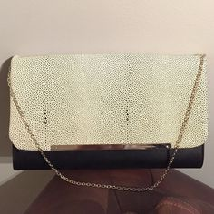 """Oversized Clutch NWOT Limited Edition clutch. Black and white pebbled flap with silver accent. Silver chain for shoulder...can be tucked in so its not seen as well. Small zipper pocket inside and large open pocket on back. 13""""W x 8H Bags Clutches & Wristlets"""